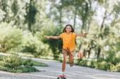 szép, boldog gyermek lovaglás gördeszka Park
