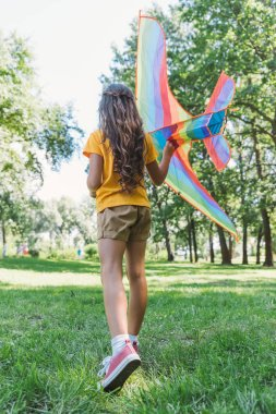 rear view of child playing with colorful kite in park