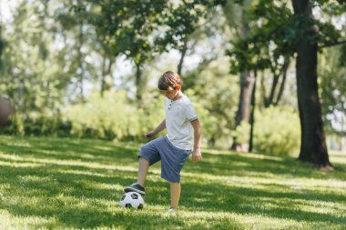full length view of cute little boy playing with soccer ball in park