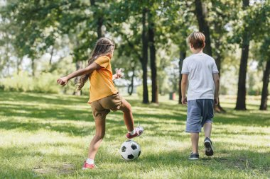 back view of children playing with soccer ball in park