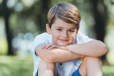 portrait of cute happy little boy sitting and smiling at camera in park