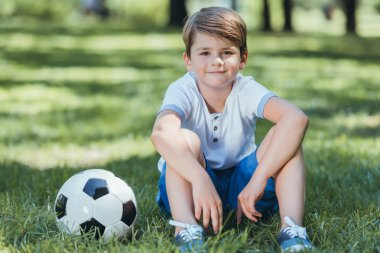 cute little boy sitting on grass with soccer ball and smiling at camera in park