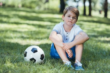 cute little boy sitting on grass with soccer ball and looking at camera in park