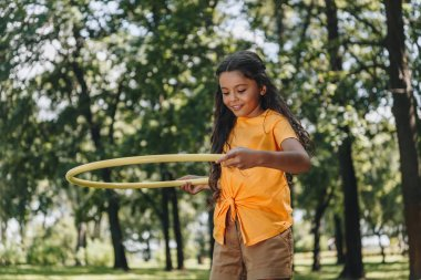 beautiful happy child playing with hula hoop in park