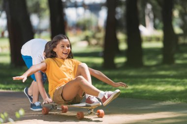 adorable happy kids having fun with longboard in park