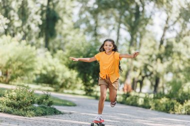 beautiful happy child riding skateboard in park