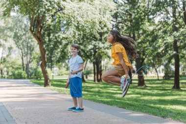 adorable happy kids playing and jumping with skipping ropes in park