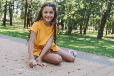 beautiful child drawing with chalk and smiling at camera in park