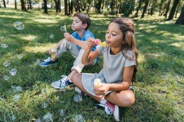 cute little kids blowing soap bubbles in park