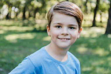 portrait of happy little boy smiling at camera in park