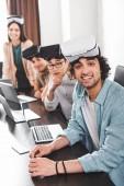 Fotografie lächelnde Gruppe multiethnischen Geschäftspartner mit virtual-Reality-Headsets am Tisch mit Laptops im modernen Büro