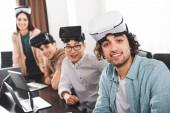 Fotografie Gruppe von multiethnischen Geschäftspartner mit virtual-Reality-Headsets am Tisch mit Laptops in modernen Büro
