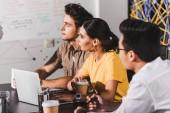 multikulturelle Geschäftspartner mit Treffen am Tisch mit Laptops in modernen Büro