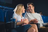 Fotografie usmívající se pár a pití nápoj, drželi se za ruce při sledování filmu v kině