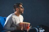 Fotografie Seitenansicht des emotionalen Menschen in 3d Brille mit Popcorn Film alleine im Kino anschauen