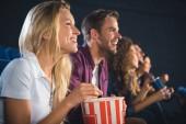 Fotografie veselí přátelé s popcorn společně sledovat film v kině