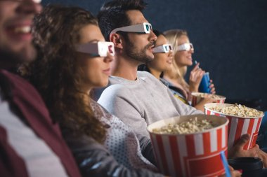 Multiethnic friends in 3d glasses with popcorn watching film together in movie theater stock vector