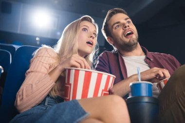 shocked couple with popcorn and soda drink watching film together in cinema