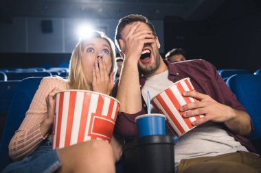 scared couple with popcorn and soda drink watching film together in cinema