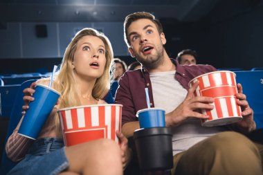 emotional couple with popcorn watching film together in cinema