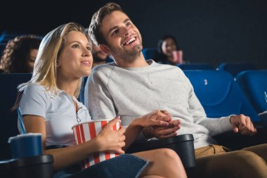 smiling couple with popcorn and soda drink holding hands while watching film together in cinema