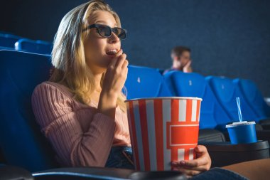 Side view of young woman in 3d glasses with popcorn watching film alone in cinema stock vector
