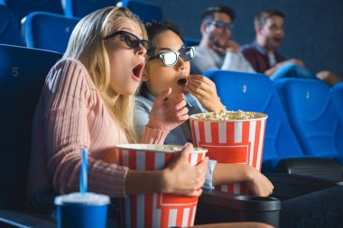 shocked multiracial women in 3d glasses with popcorn watching film together in movie theater