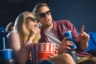 Emotional couple in 3d glasses with popcorn watching film together in cinema stock vector