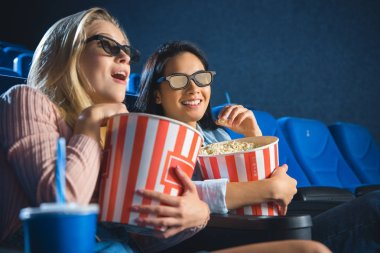emotional multiracial women in 3d glasses with popcorn watching film together in movie theater
