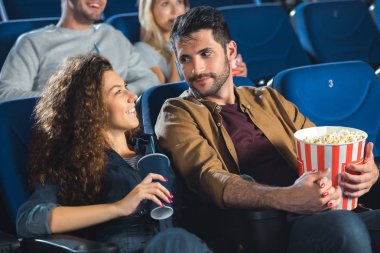 Couple with popcorn watching movie together in cinema stock vector