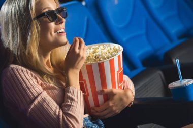 Side view of smiling woman in 3d glasses with popcorn watching film alone in cinema stock vector