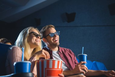cheerful couple in 3d glasses with popcorn watching film together in cinema