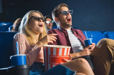 Shocked couple in 3d glasses with popcorn watching film together in cinema stock vector