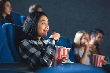 emotional asian woman with popcorn watching movie in cinema
