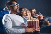 Fotografie Šokovaný mnohonárodnostní přátelé v 3d brýle s popcorn společně sledovat film v kině
