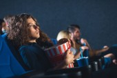 Fotografie side view of scared woman with popcorn watching movie in cinema