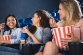 Fotografie Happy mnohonárodnostní ženy s popcorn společně sledovat film v kině