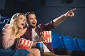 Fotografie Šokovaný pár s popcorn a limonádu skleničku sledovat film v kině