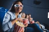 Fotografie selektiven Fokus der lächelnden Asiatin in 3d Brille mit Popcorn im Kino