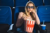 Porträt einer fokussierten Frau in 3D-Gläsern mit Popcorn, die sich allein im Kino Filme ansieht