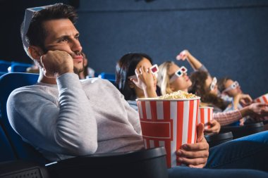 bored multiethnic friends with popcorn watching film together in movie theater