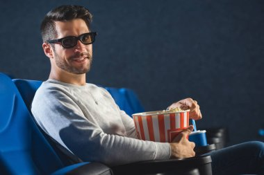 side view of smiling man in 3d glasses with popcorn in cinema