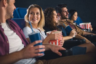 cheerful multiethnic friends with popcorn watching film together in movie theater