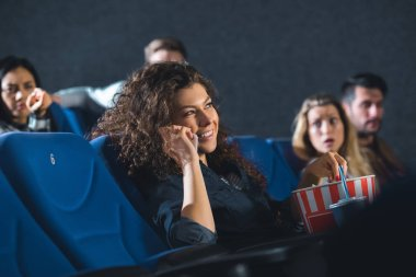 smiling woman talking on smartphone while watching movie in cinema