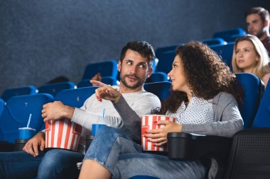 couple with popcorn watching movie together in cinema
