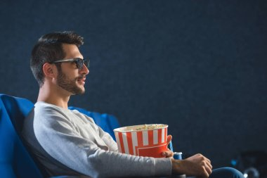 Side view of young man in 3d glasses with popcorn watching film in cinema stock vector