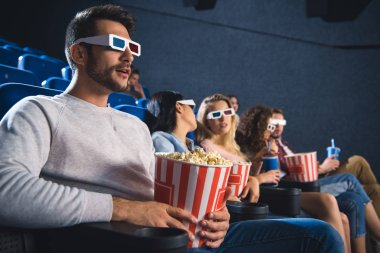 selective focus of multiethnic friends in 3d glasses with popcorn watching film together in movie theater