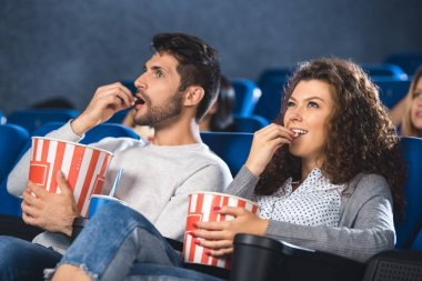 Couple eating popcorn while watching film together in cinema stock vector