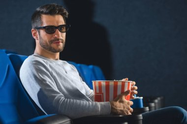 Side view of young man in 3d glasses with popcorn in cinema stock vector