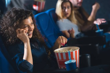 woman with popcorn talking on smartphone while watching movie in cinema